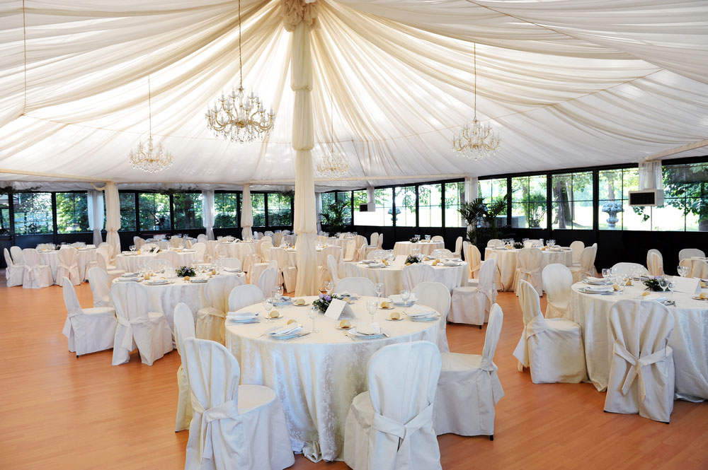 Tables and chairs placed under a white tent