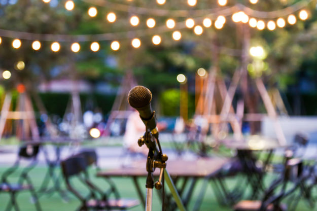 A microphone on an empty stage at an outdoor event with bistro lighting