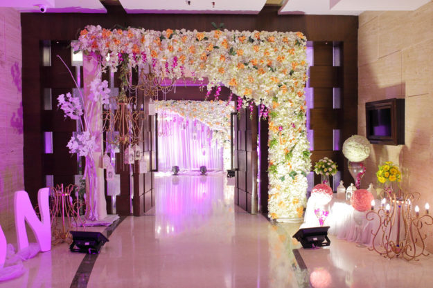 A wedding entrance with flowers and uplighting.